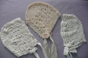 A trio of hand-crafted baby bonnets.