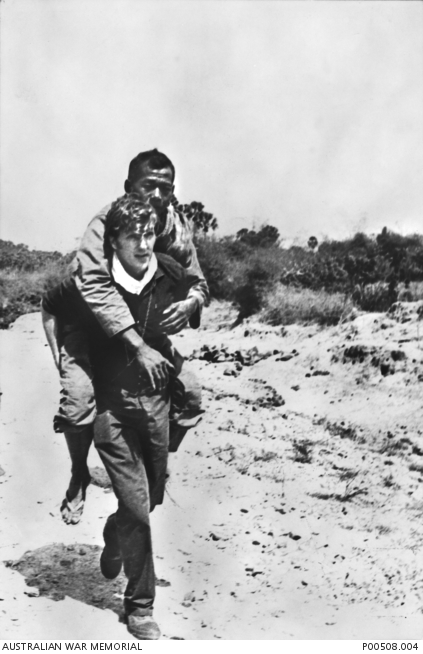 Phnom Penh, Cambodia, 1971. Australian cameraman Neil Davis carrying a wounded Cambodian soldier out of action. http://trove.nla.gov.au/work/165129872 Copyright unknown.