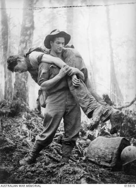 30 July 1943, Corporal Leslie (Bull) Allen MM, aged 26 of Ballarat, Victoria, carrying out an injured American soldier, one of 12 he retrieved. He was awarded the US Silver Star and had already received his Military Medal (MM) on 7 February 1943, at Crystal Creek, Wau. Negative by G Short, copyright expired. Mt Tambo, New Guinea. AWM image 015515
