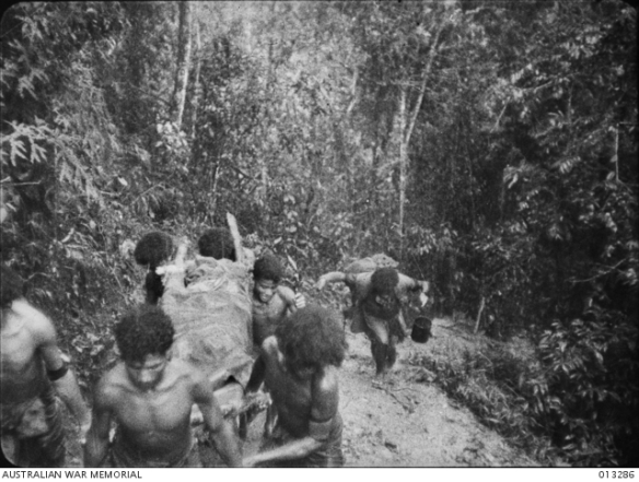 Bearers (called Fuzzy Wuzzy angels) carrying a wounded soldier up a steep, muddy slope, Papua.