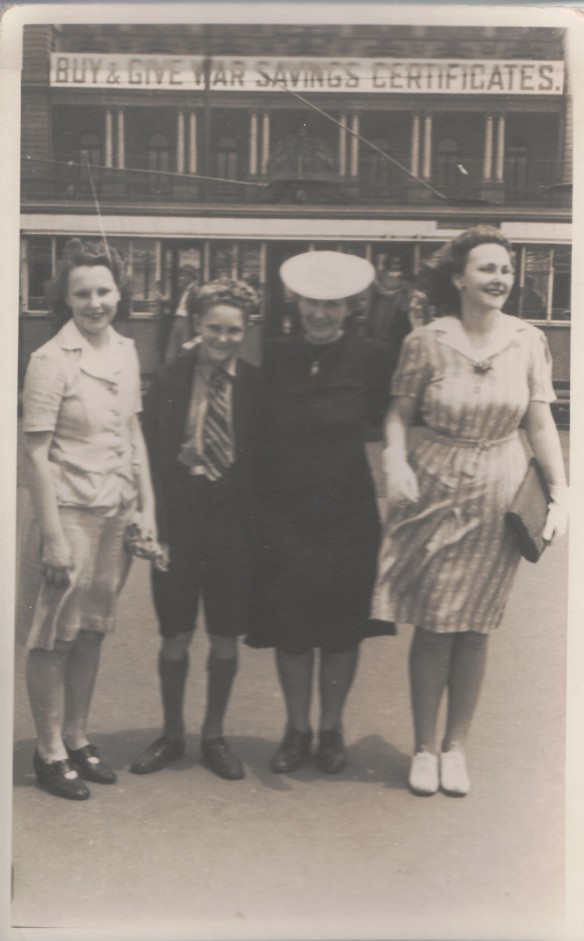 The Sydney siblings, Nora, Kevin and Marie with their aunty Nellie (in the hat).  I like the war bonds notice on the building.